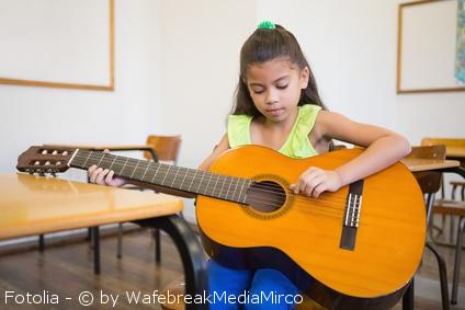 Enfant avec une guitare trop grande